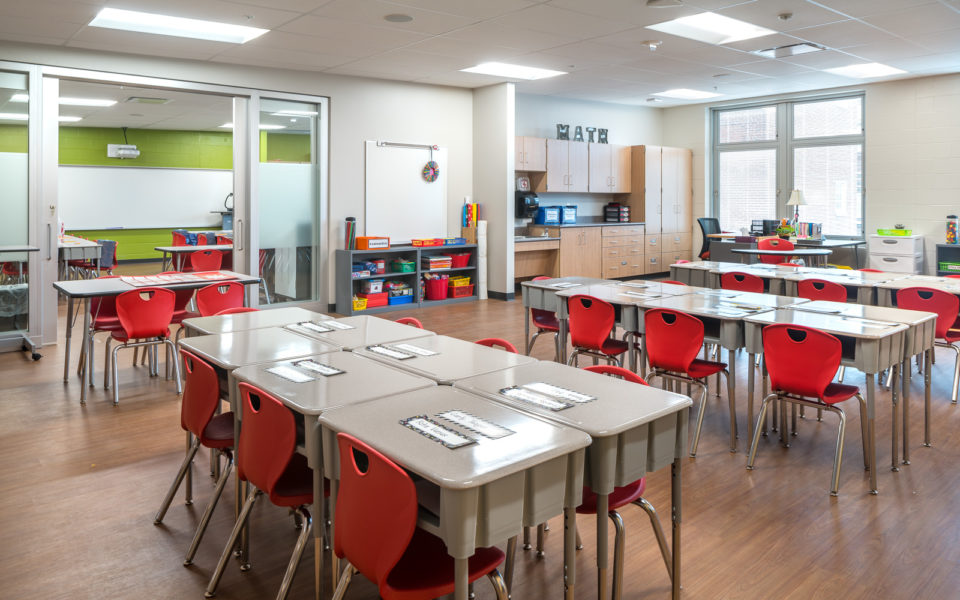 A brightly-lit elementary classroom, ready for the school year. The desks are arranged in clusters of seven, with the teachers desk and pale wood cabinets are in the fair right corner near the windows. The chairs are a cheerful red, and there are brightly colored bins and books on the shelves along the wall. The door is glass, and an extra bit of glass wall next to the door lets in extra light.
