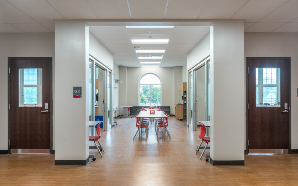 An Extended Learning Center. This space between two classrooms has large arched window in the center of the far wall, with a bookshelf beneath. Near the window is a circular table with four red chairs. A long table stretches the middle of the room, with eight red chairs tucked in, four on each side. Rectangles of fluorescent lighting from the ceiling. There are doors on either side of the classroom, large glass doors that lead to the standard classrooms.
