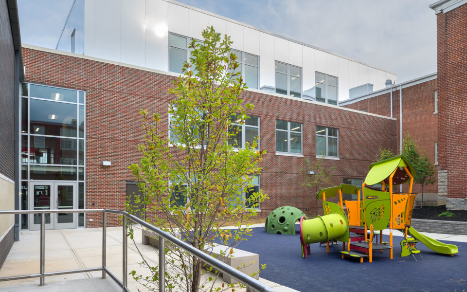 A small school playground in a middle courtyard. The climbing structure is lime green and vivid orange, with tunnels, and a small slide. Beneath the climbing structure is navy blue rubber playground surfacing. The walls of the surrounded school are red brick for the first two stories, and then the third story is a mirrored surface, making the top of the building seem to connect with the blue sky.