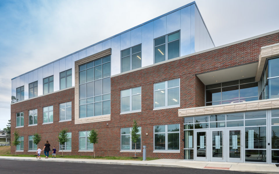 The new entrance to Amity Elementary. The three-story structure has clean lines and large windows. The first two stories have a facade of red brick, and the third story has a facade of mirrors so that the top story seems to connect with the sky. There are ribbons of beige stone accents.