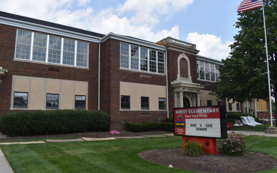 The front of Amity Elementary prior to the renovations of Summer 2018. A red sign surrounded by a circular garden on the front lawn, boasts of