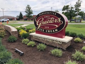 Exterior sign of Hilliard Graeter's logo surrounded by modest landscaping of shrubs and brick walls, as well as lush green grass.