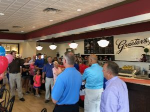 A crowd of people in brightly colored shirts standing in line at the counter of a classic ice cream parlor, waiting for their ice cream at the grand opening of the Hilliard Graeter's.