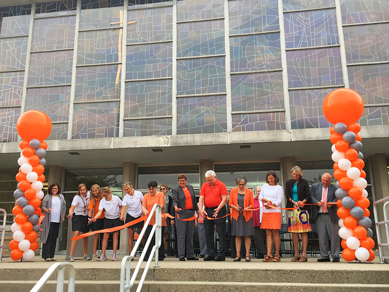 A group of high school girls and middle-aged to elderly adults stand in front of a large building, as part of the ceremonial Mercy McAuley ribbon cutting. There are columns of orange gray and white balloons.