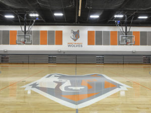 "A school gymnasium. The wolf mascot is painted on the center of the court in gray, white and orange. The mascot image is also painted on the wall, with ""Mercy McAuley Wolves"" printed beneath, and surrounded by gray and orange wall padding. There are two basketball hoops, one on either side of the frame. The gray bleachers are in the background, tucked away. The ceiling is black."
