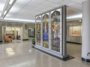 An historic three-paneled stained glass window on display in a school lobby. The stained glass depicts the Mother Mary in the center, holding the baby Jesus, with an angel on either side. The school lobby is well-lit, with an overall cool gray coloring, and a chair outside of the office entrance. The chair is upholstered in red and yellow striped fabric. There are two potted plants in the lobby.