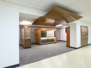"A ""Legacy Center."" Two large entrances lead off from a main lobby area and into a room with gray carpet and large wooden display cases. Historic yearbooks are on display in a custom cabinet, and curved wood panels hang from the ceilings, serving as a transition piece between lobby and Legacy Center."