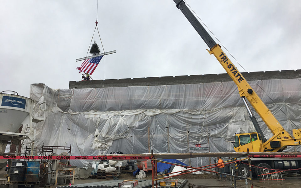 A large yellow crane lifts a ceremonial beam onto the top of Amity Elementary. The beam also holds a small fir tree, and an American flag hangs from the bottom of the beam.