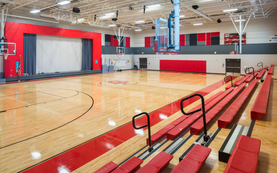 School gymnasium with bleachers open and basketball hoops lowered