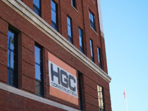 A red brick building with a large sign bearing HGC Construction's logo