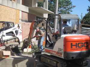 An orange and white mini excavator with HGC logo at work on construction site.