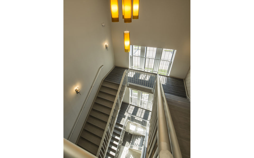 Looking down on large stairwell. Modern accent light fixture adds a splash of warm color to the otherwise cool and gray space. Windows let in lots of natural light.
