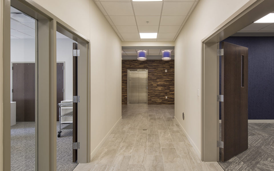 Hallway leading to an elevator, and open doors on either side of the hallway. Pale tile floors of the hall, carpeted rooms.