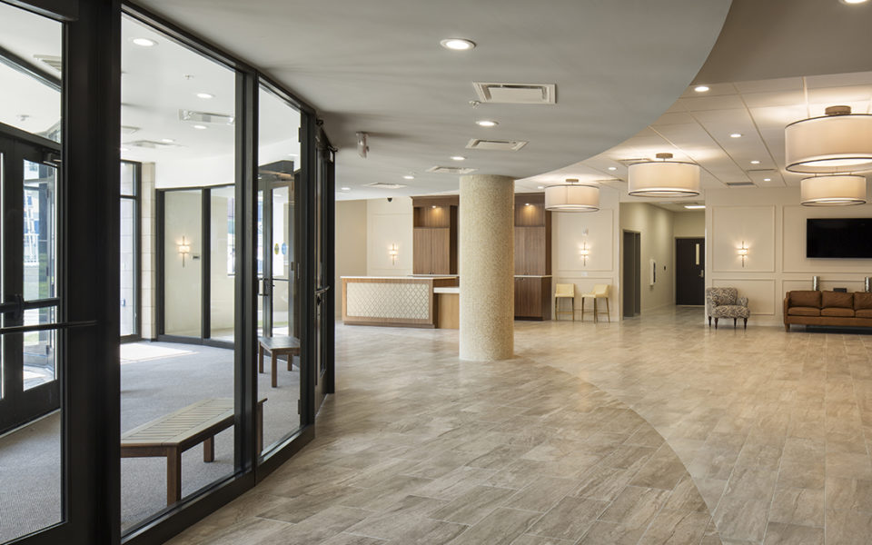 Lobby of a church with neutral colors and large curved glass entry to the left, and welcome desk.