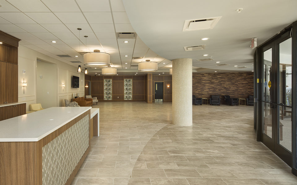 Large lobby of a church. Lots of natural light, neutral tones. Welcome desk to the left, seating areas in the back.
