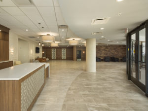 Large, neutral-toned lobby with columns, beige tile on floors, and seating along walls.