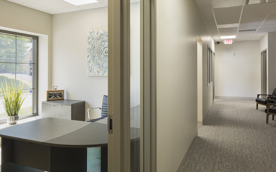 Carpeted hallway of office area. An ajar door allows a view of a well-lit office to the left. Neutral tones, clean lines, and lots of light.