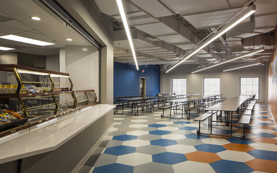 Cafeteria. Hexagon tiles of blue, orange, gray and white. Three rows of tables line the room, and three large windows along the back wall illuminate the room.