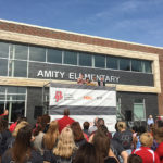 "A large crowd faces away from the camera to watch a speaker standing on top of scaffolding in front of a newly constructed school building. The building has a section of gray brick outlined by beige stone, and surrounded by a large section of red brick. ""Amity Elementary"" is affixed in large metal letters to the building facade. It is a sunny day with bright blue sky."