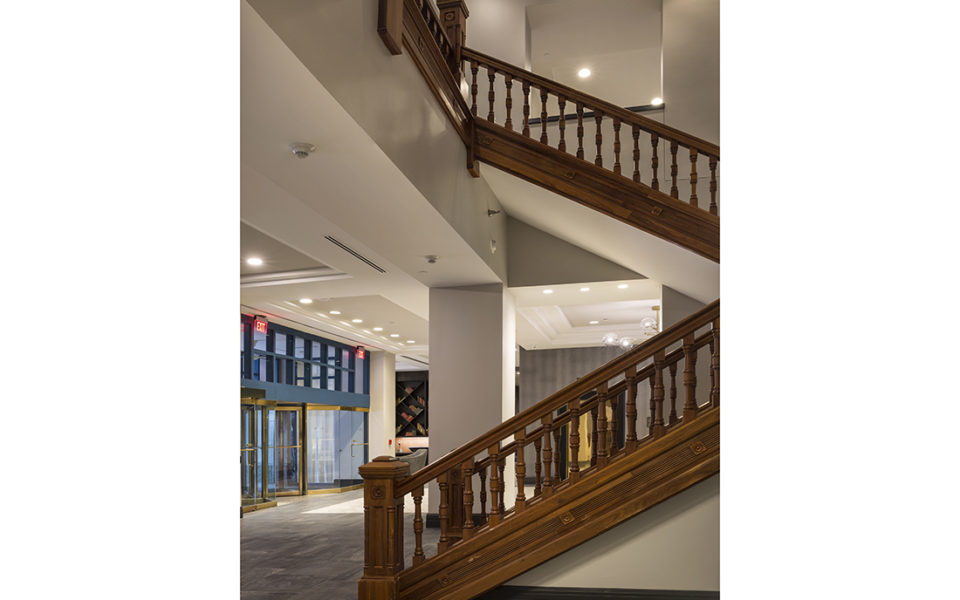 Large wooden staircase near entrance of hotel.