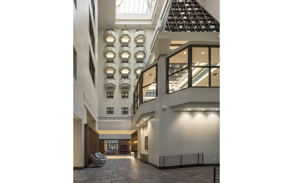 Grand foyer in a hotel; six stories of guest room windows look down on the atrium.