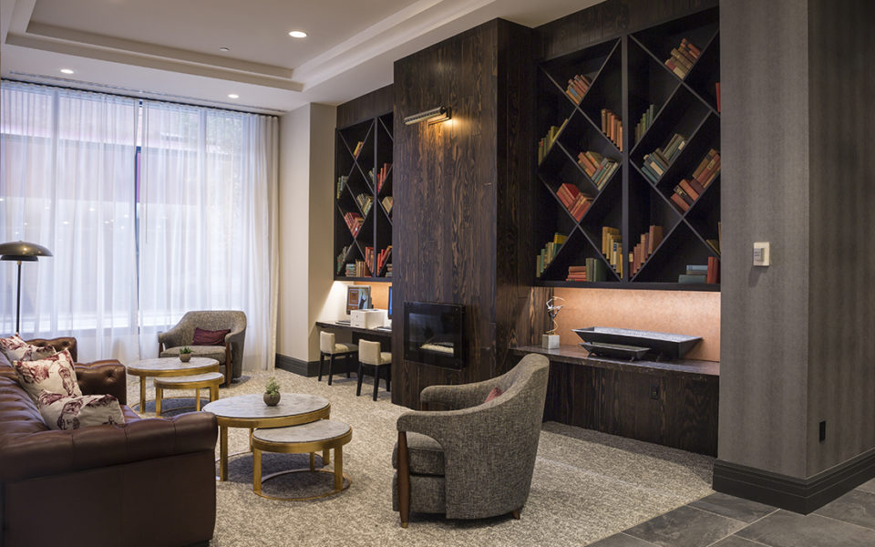 Hotel lounge with dark wooden shelves with books and neutral arm chairs