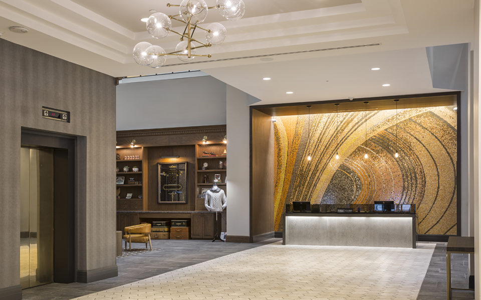 Grand foyer and lobby of a hotel with a dramatic mosaic behind the hospitality desk