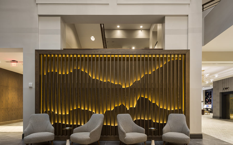Hotel lobby with four arm chairs and artistic wooden wall display