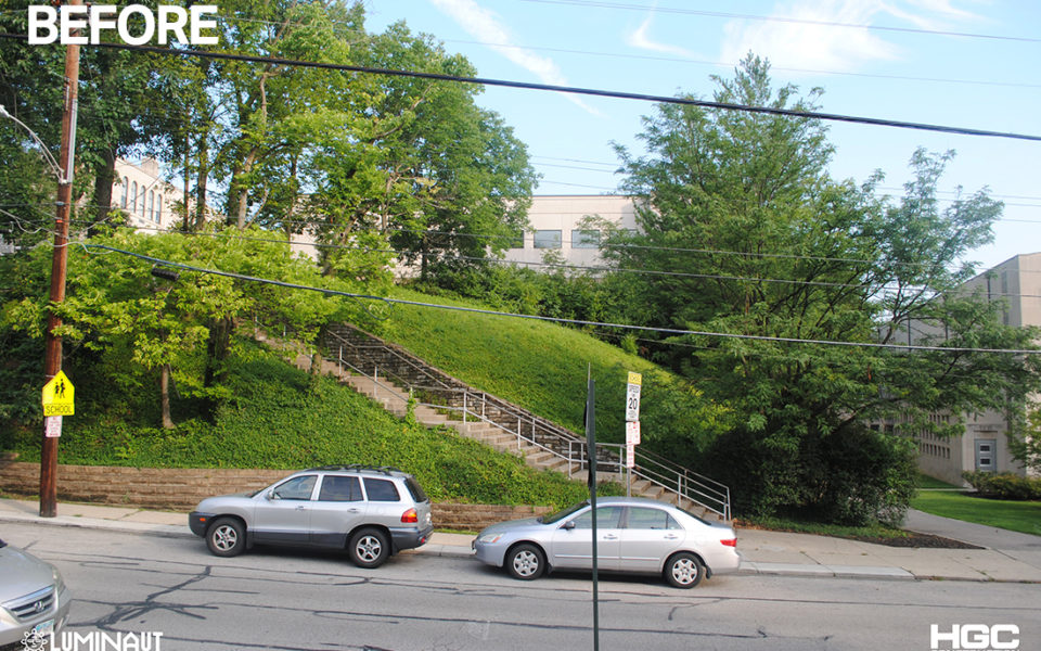 A grassy hill with a large concrete staircase.