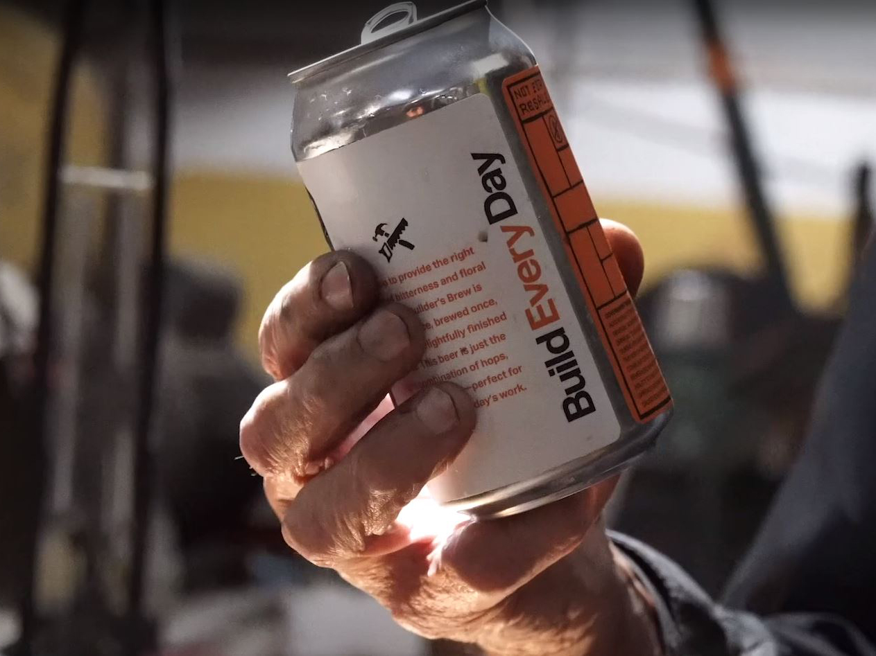 weathered hand holds a can of Builders Brew