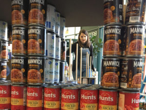 Woman working on Train sculpture made of canned goods