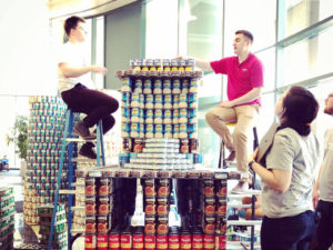 Team working on Train sculpture made of canned goods