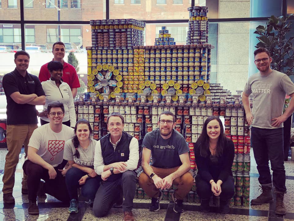 Team in front of train sculpture made of cans