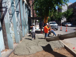 Workers pour sidewalk in front of Columbia Building