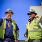 two workers standing and smiling