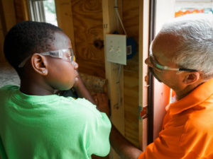 Terry Prosser teaches a young child basic carpentry