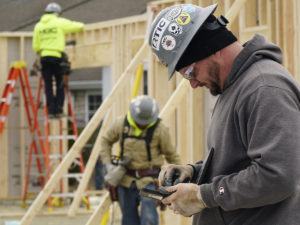 Worker consults technology on Maple Knoll Village job site