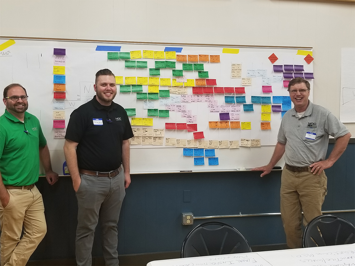 Warren County team Jacob Reeves, Braden, and Tom France in front of completed pull plan schedule