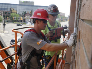 workers repairing exterior of Fidelity building in Norwood