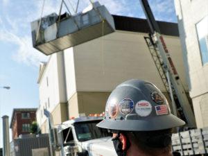 HGC team member watches crane life HVAC equipment