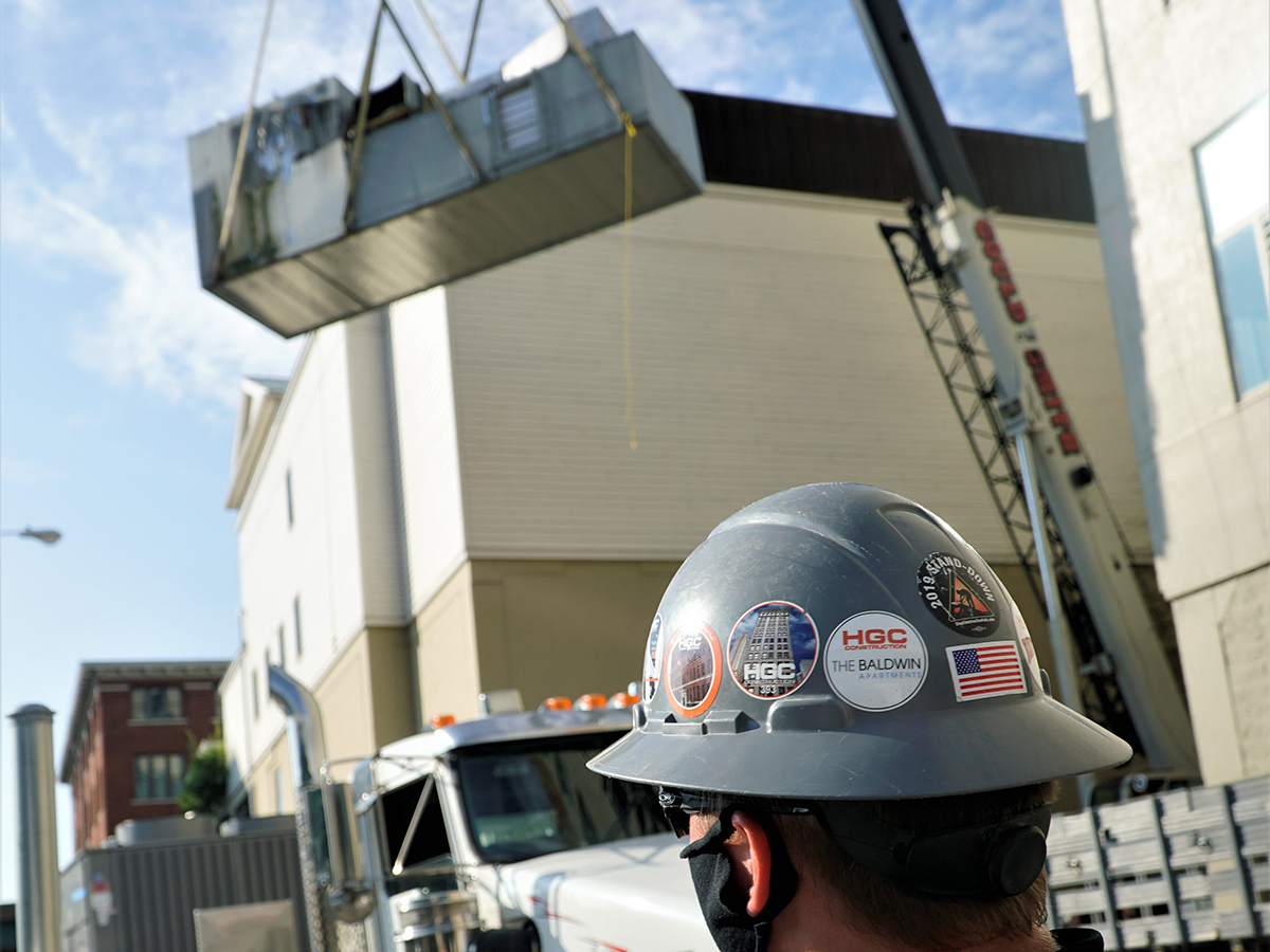 HGC team member watches crane life HVAC equipment