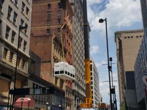 Crane lifting equipment to roof of Ingalls