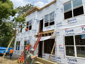 People standing in front of theframe of building with Tyvek sheeting on the outside