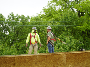 two people standing on a roof tied off with harnesses