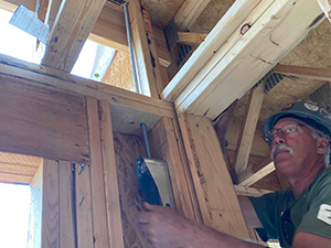 person using level on wood framing