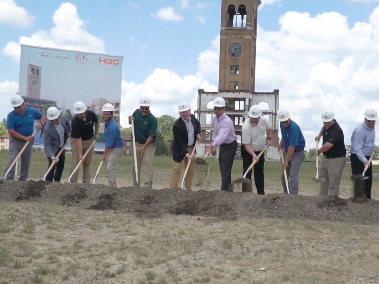 people breaking ground at a construction site with clock tower in background